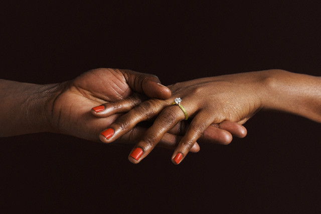New York, NY, USA --- African American woman with engagement ring holding fiancee's hand --- Image by © Roy Hsu/Blend Images/Corbis